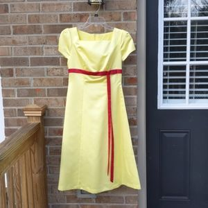 Gorgeous yellow dress with red accent.